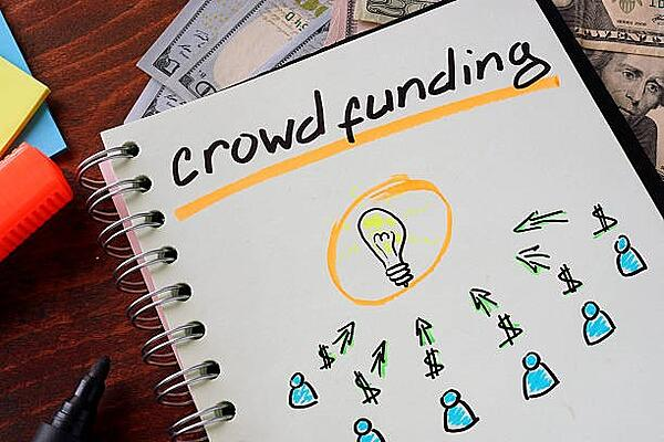 Notebook with crowdfunding sign on a table. Business concept.